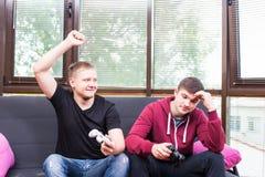 Dos hombres jovenes hermosos que juegan a los videojuegos mientras que se sienta en el sofá Imagenes de archivo