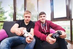 Dos hombres jovenes hermosos que juegan a los videojuegos mientras que se sienta en el sofá Foto de archivo libre de regalías