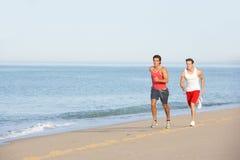 Dos hombres jovenes que activan a lo largo de la playa Foto de archivo