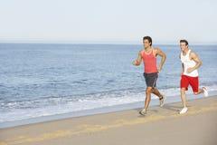 Dos hombres jovenes que activan a lo largo de la playa Foto de archivo libre de regalías