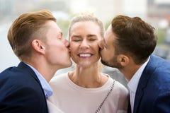 Dos hombres jovenes que besan a la mujer en sus mejillas Imagenes de archivo