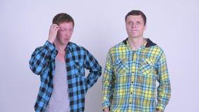 Dos hombres jovenes que consiguen malas noticias y que miran trastorno junto metrajes