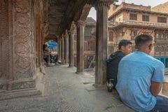 Dos hombres jovenes que discuten en los pasos de un templo fotos de archivo libres de regalías