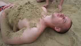 Dos hombres jovenes que juegan con la arena en la playa, una lanzan la arena otra almacen de metraje de vídeo