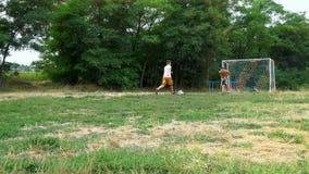 Dos hombres jovenes que juegan a fútbol fuera de la ciudad almacen de metraje de vídeo