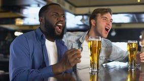 Dos hombres jovenes que miran la competencia de deporte en el pub, vidrios de cerveza que tintinean, afición almacen de video