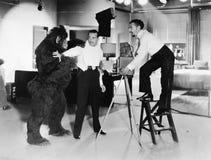 Dos hombres jovenes que miran ser atacado temido por un gorila (todas las personas representadas no son vivas más largo y ningún  Fotos de archivo libres de regalías