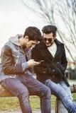 Dos hombres jovenes que sientan el mensaje de texto del SMS de la lectura Imágenes de archivo libres de regalías