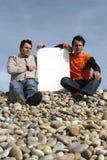 Dos hombres jovenes que sostienen la tarjeta blanca Imagenes de archivo