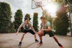 Dos hombres jovenes que tienen un juego del baloncesto Imagen de archivo libre de regalías