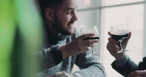 Dos hombres jovenes que tienen una conversación activa, alto cinco, alegrías y tienen un sorbo de cerveza de cerveza dorada super almacen de metraje de vídeo