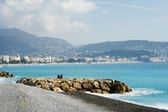 Dos hombres jovenes se sientan en las piedras contra el contexto del mar azul Agradable, Francia, la niebla azul de la luz de la  foto de archivo