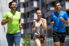 Dos hombres jovenes y mujer que corren en el ambiente urbano Foto de archivo