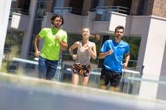 Dos hombres jovenes y mujer que corren en el ambiente urbano Fotografía de archivo