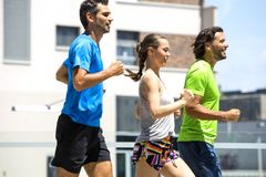 Dos hombres jovenes y mujer que corren en el ambiente urbano Foto de archivo libre de regalías