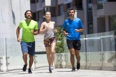 Dos hombres jovenes y mujer que corren en el ambiente urbano Imagen de archivo libre de regalías