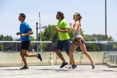 Dos hombres jovenes y mujer que corren en el ambiente urbano Imagenes de archivo