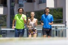 Dos hombres jovenes y mujer que corren en el ambiente urbano Fotos de archivo libres de regalías