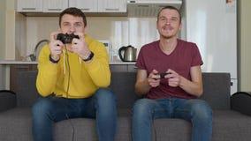 Dos hombres juegan entusiasta al videojuego almacen de metraje de vídeo