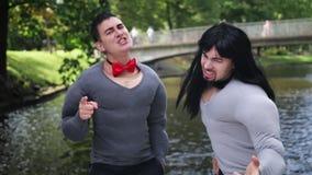 Dos hombres lindos jovenes en m?sculo falso rellenaron los trajes carism?ticamente cantan en barco almacen de metraje de vídeo