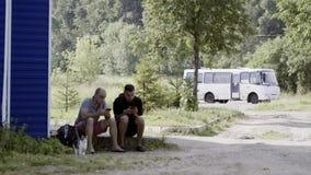 Dos hombres maduros se sientan en el encintado que mira sus smartphones el área del suburbio metrajes