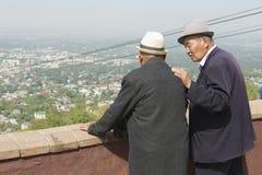 Dos hombres mayores del kazakh hablan y disfrutan de la visión a la ciudad de Almaty en Almaty, Kazajistán Foto de archivo