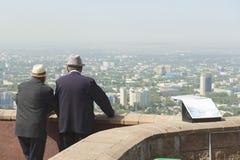 Dos hombres mayores del kazakh hablan y disfrutan de la visión a la ciudad de Almaty en Almaty, Kazajistán Imagen de archivo