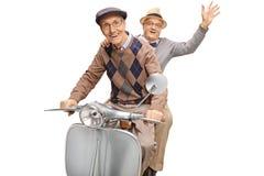 Dos hombres mayores en una vespa del vintage, una que agita foto de archivo libre de regalías