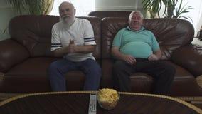 Dos hombres mayores maduros que se sientan en el sof? de cuero marr?n que ve la TV El hombre emocional barbudo es un fan del equi almacen de video