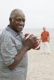 Dos hombres mayores que juegan a fútbol americano en la playa Foto de archivo libre de regalías