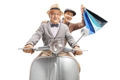 Dos hombres mayores que montan en una vespa del vintage, una compras que celebran foto de archivo