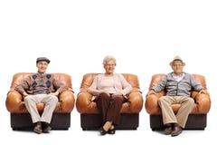 Dos hombres mayores y mujer mayor que se sientan en las butacas de cuero Foto de archivo libre de regalías