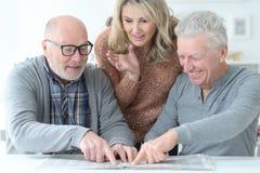 Dos hombres mayores y mujer que usa el ordenador portátil Fotografía de archivo