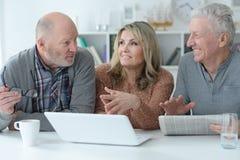 Dos hombres mayores y mujer que usa el ordenador portátil Imagen de archivo libre de regalías