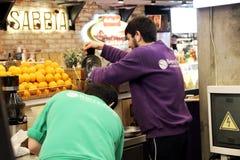 Dos hombres preparan el jugo natural recientemente exprimido, zona de restaurantes en el mercado central imagen de archivo libre de regalías