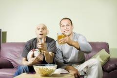 Dos hombres que beben la cerveza y que miran fútbol en la TV Imagen de archivo libre de regalías