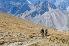 Dos hombres que caminan en las montañas de Himalaya Foto de archivo