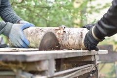Dos hombres que cortan la madera usando la sierra circular Foto de archivo libre de regalías