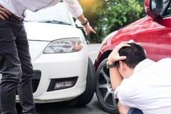 Dos hombres que discuten después de una colisión del tráfico del accidente de tráfico en el ro fotografía de archivo
