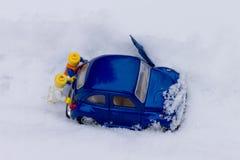 Dos hombres que empujan el coche pegado en nieve Modelos del juguete Foto de archivo
