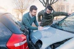 Dos hombres que escriben una demanda de seguro de coche fotografía de archivo libre de regalías