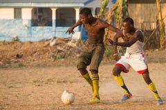 Dos hombres que juegan a fútbol en pueblo africano Imagen de archivo