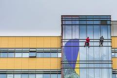 Dos hombres que limpian ventanas del edificio de oficinas en Bucarest Imagen de archivo libre de regalías