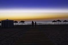 Dos hombres que llevan a cabo las manos, caminando delante de la puesta del sol en el bea Imagenes de archivo