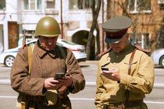 Dos hombres que llevan el uniforme militar del vintage, mandando un SMS en smartphones Fotografía de archivo