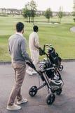 Dos hombres que llevan a los clubs de golf en las bolsas de golf y que caminan en el campo de golf Foto de archivo