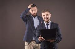Dos hombres que miran el ordenador portátil Imagen de archivo