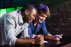 Dos hombres que miran el teléfono móvil y que sonríen en el contador de la barra Foto de archivo