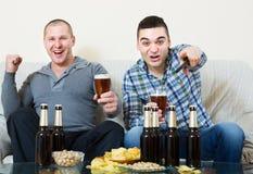 Dos hombres que miran fútbol con la cerveza interior Foto de archivo libre de regalías