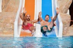 Dos hombres que montan abajo de los diapositiva-amigos de un agua que gozan de un tubo del agua montan Foto de archivo libre de regalías